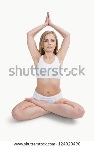 Portrait of young woman in sportswear joining hands over head against white background