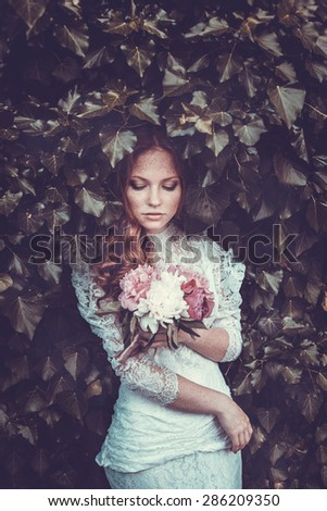 Portrait of young woman in the spring time. Almond flowers blossoms. Girl dressed in white like a bride. - stock photo