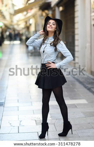 Portrait of young woman in urban background wearing casual clothes and hat carrying a bag - stock photo