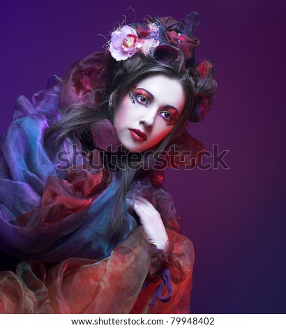 Portrait of young woman in violet shawl and with exotic flowers in her hair.