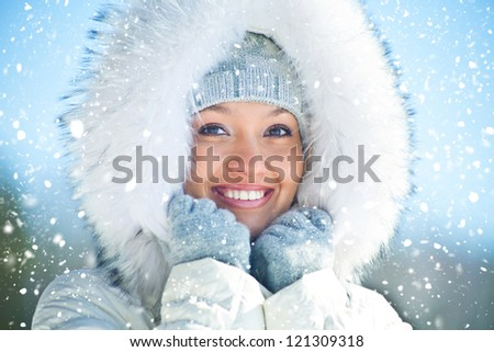 Portrait of young woman in white fur in winter - stock photo