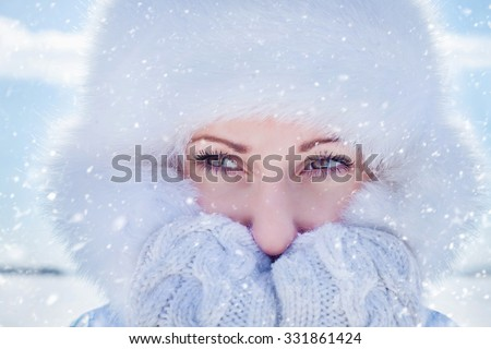 Portrait of  young woman in winter winter clothing and fur cap - stock photo