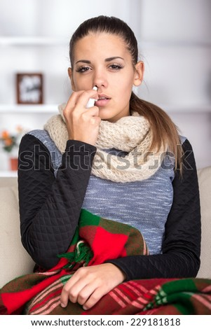 Portrait of young woman is using nose spray. - stock photo