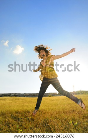 Portrait of young woman jumping of joy on yellow grass field