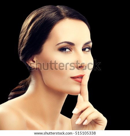 Portrait of young woman keeping finger on her lips and asking to keep quiet or secret, isolated against black background. Brunette model - beauty, glamour, fashion, modeling, cosmetics concept.