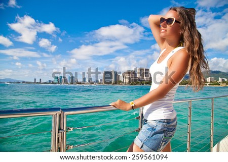 Portrait of young woman leaning on yacht railings, Oahu, Hawaii, USA. Girl on travel vacation holidays relaxing on Hawaiian resort. Summer cruise holidays - stock photo