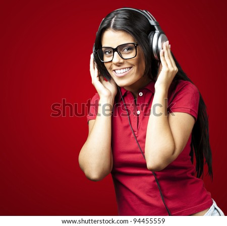 portrait of young woman listening to music against a red background - stock photo
