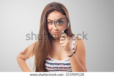 portrait of young woman looking through a magnifying glass - stock photo