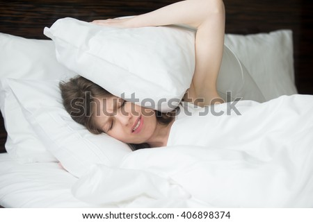 Portrait of young woman lying in bed and covering her ears with pillows from noise. Female model with irritated expression having problems with sleep