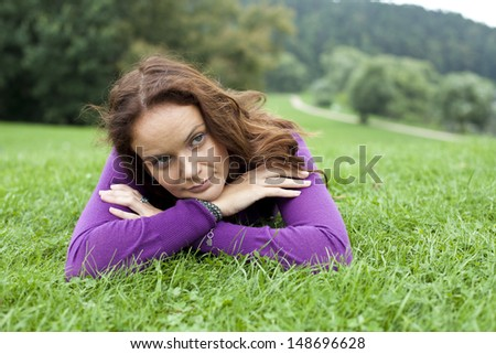 Portrait of young woman lying on a green lawn - stock photo