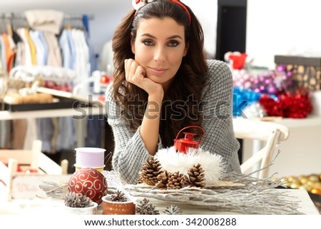 Portrait of young woman making decoration by hand, looking at camera. - stock photo