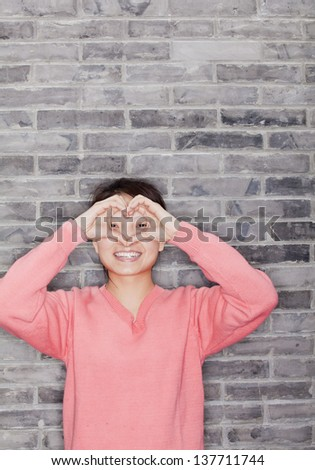 Portrait of Young Woman Making Heart with Fingers - stock photo