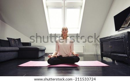 Portrait of young woman meditating in lotus position at home. Caucasian female model sitting with legs crossed on living room floor. - stock photo