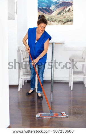 Portrait Of Young Woman Mopping Floor At Home . Cleaning Service
