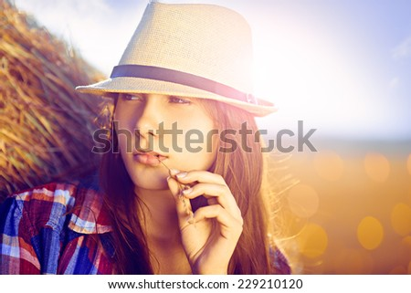 Portrait of young woman next to a stack of hay in sunlight; lens flare - stock photo