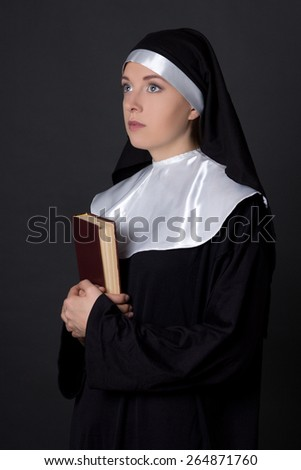 portrait of young woman nun holding bible over grey background - stock photo