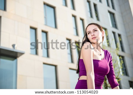 Portrait of young woman on street with buildings in background - stock photo
