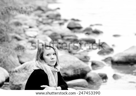 Portrait of young woman on the bank of the lake - stock photo