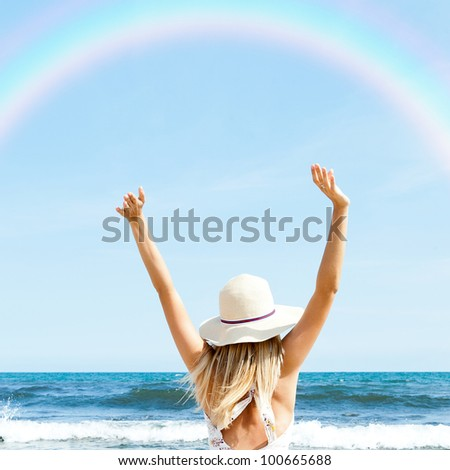 Portrait of young woman on the beach near the sea sitting with hands up wearing sophistical dress and hat looking at rainbow. Photo from behind - stock photo
