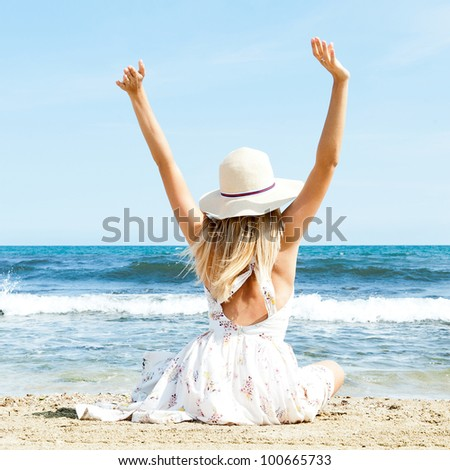 Portrait of young woman on the beach near the sea sitting with hands up wearing sophistical dress and hat. Photo from behind