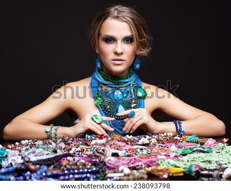 Portrait of young woman over heap of bijouterie on the table - stock photo