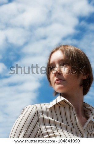 Portrait of young woman over the sky - stock photo