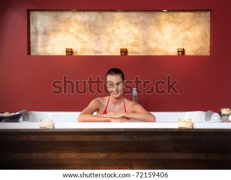 Portrait of young woman posing in bikini in wellness bath, smiling at camera.? - stock photo