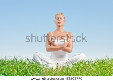 Portrait of young woman practicing yoga outdoors. - stock photo