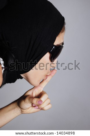 Portrait of young woman profile with finger on lips - stock photo