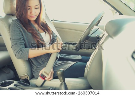 portrait of young woman putting on a seatbelt for safety - stock photo