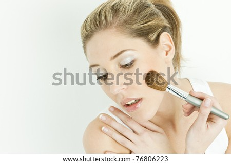 portrait of young woman putting on face powder - stock photo