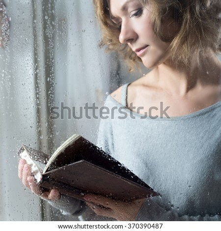 Portrait of Young woman reading throw the rain drops