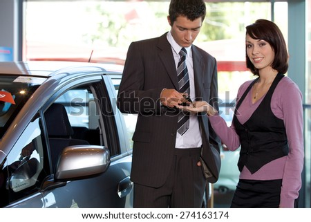 Portrait of young woman receiving car key from car salesman