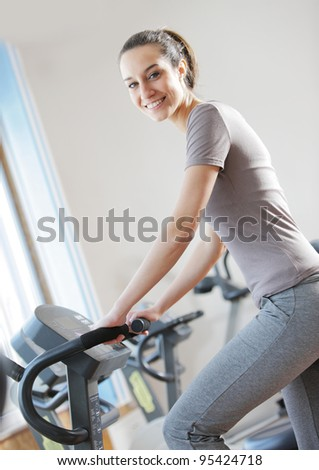 portrait of  young woman riding an exercise bike - stock photo