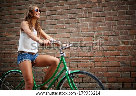 Portrait of young woman riding bicycle against brick wall - stock photo
