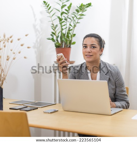 Portrait of young woman (20s) holding a smartphone sitting behind a laptop computer on wood desk. She is enjoying and looking at camera in office.