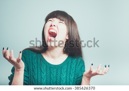 Portrait of young woman screaming hysterically, isolated on a gray background - stock photo