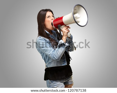portrait of young woman screaming with megaphone against a grey background