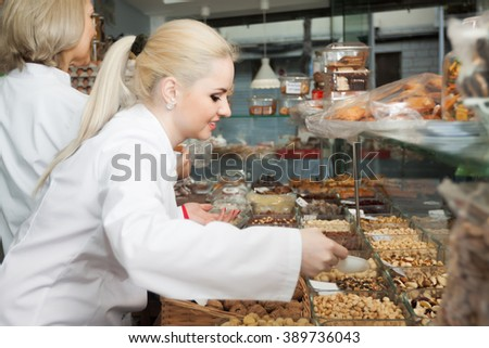 Portrait of young woman selling nuts and pastry in shop