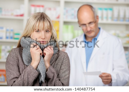 Portrait of young woman shivering with male pharmacists reading prescription paper at pharmacy - stock photo