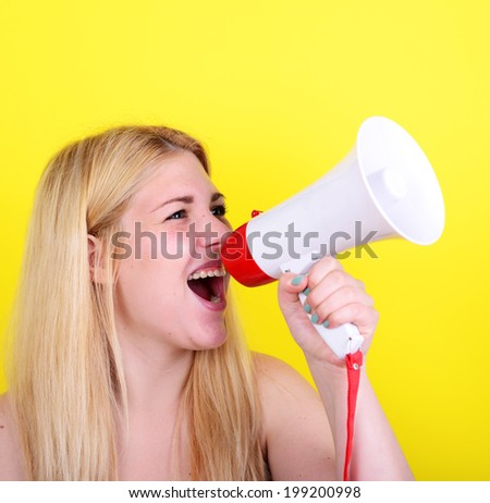 Portrait of young woman shouting with a megaphone against yellow background