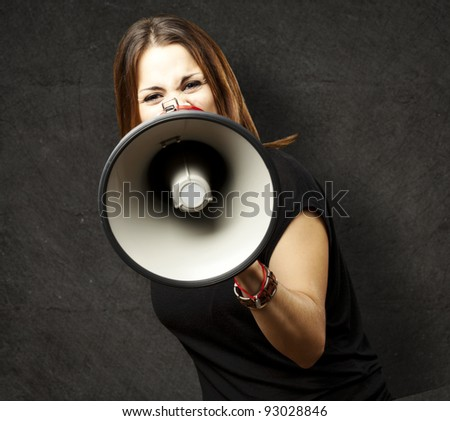 portrait of young woman shouting with megaphone against a grunge wall