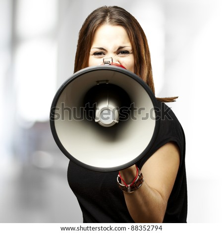 portrait of young woman shouting with megaphone indoor