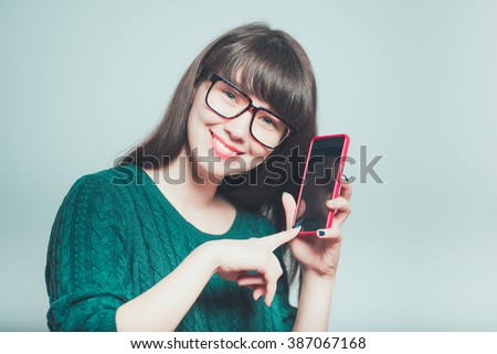 portrait of young woman shows a look at the phone, hipster isolated on a gray background - stock photo