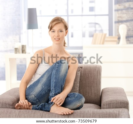 Portrait of young woman sitting at sofa at home, looking at camera, smiling. - stock photo