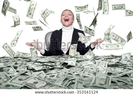 portrait of young woman sitting behind the table full of cash - stock photo
