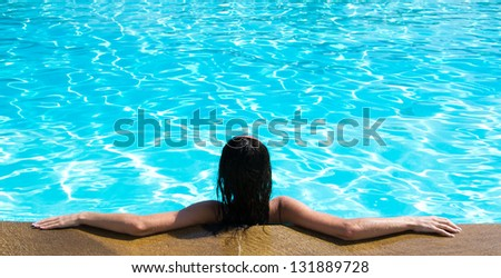 Portrait of young woman sitting in swimming pool - stock photo