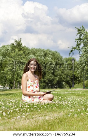 Portrait of young woman sitting on a green lawn