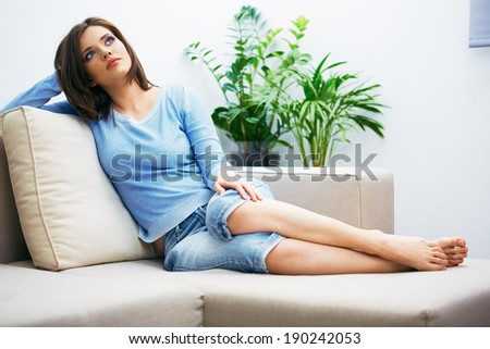 Portrait of young woman sitting on couch at home. Relaxing girl.