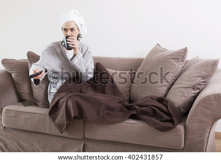 Portrait Of Young Woman Sitting On Couch Watching Television